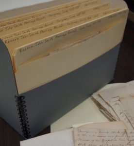 Folders containing documents placed into archival safe box for proper storage.
